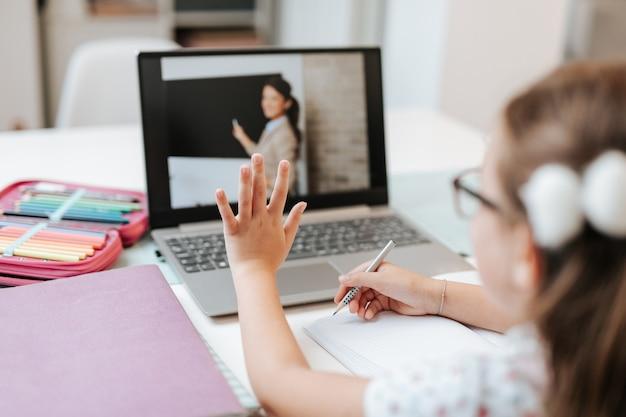 Молодая девушка начальной школы смотрит онлайн-класс образования. образовательная концепция изоляции коронавируса или covid-19.