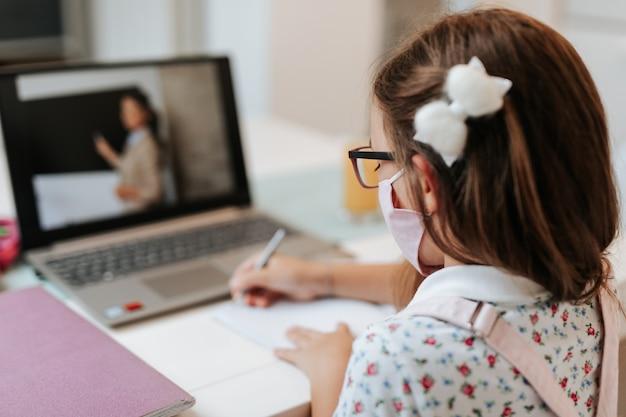 얼굴 보호 마스크를 쓴 어린 초등학교 여학생이 온라인 교육 수업을 보고 있습니다. 코로나바이러스 또는 코비드-19 잠금 교육 개념.