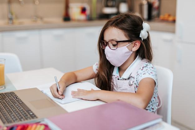 Молодая девушка начальной школы с защитной маской для лица, наблюдая за онлайн-классом образования. образовательная концепция изоляции коронавируса или covid-19.