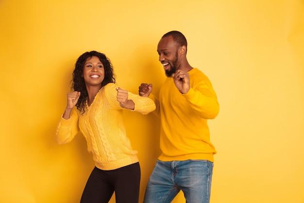 黄色の背景に明るいカジュアルな服を着た若い感情的なアフリカ系アメリカ人の男性と女性。美しいカップル。人間の感情、顔の表現、関係、広告の概念。踊り、歌う。