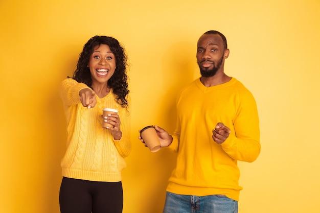 黄色の背景に明るいカジュアルな服を着た若い感情的なアフリカ系アメリカ人の男性と女性。美しいカップル。人間の感情、顔の表現、関係、広告の概念。コーヒーを飲み、指さします。