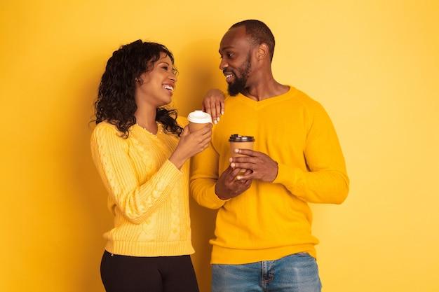 노란색 배경에 밝은 캐주얼 옷에 젊은 감정적 인 아프리카 계 미국인 남자와 여자. 아름다운 커플. 인간의 감정, 얼굴 expession, 관계, 광고의 개념. 함께 커피를 마시고 있습니다.