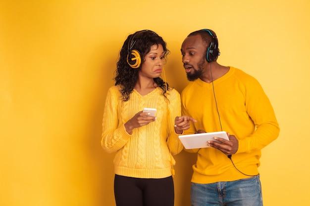 黄色の背景に明るいカジュアルな服を着た若い感情的なアフリカ系アメリカ人の男性と女性。美しいカップル。人間の感情、顔の表現、関係、広告の概念。タブレットとスマートフォンを使用します。