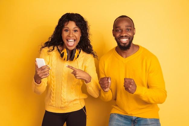 노란색 배경에 밝은 캐주얼 옷에 젊은 감정적 인 아프리카 계 미국인 남자와 여자. 아름다운 커플. 인간의 감정, 얼굴 expession, 관계의 개념. 스마트 폰에서 가리키는 충격.