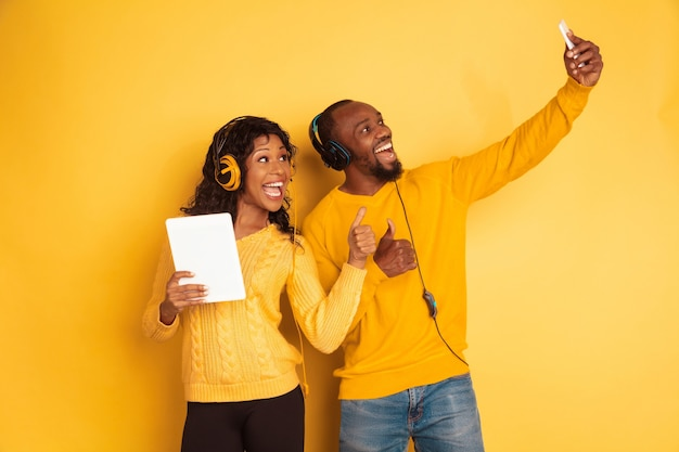 노란색 공간에 밝은 캐주얼 옷에 젊은 감정적 인 아프리카 계 미국인 남자 그리고 여자. 아름다운 커플