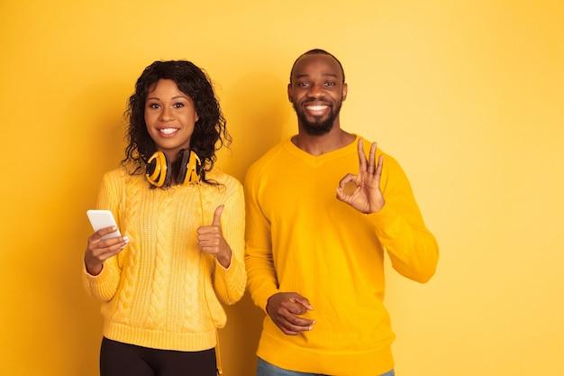 Молодой эмоциональный афро-американский мужчина и женщина в яркой повседневной одежде на желтом пространстве