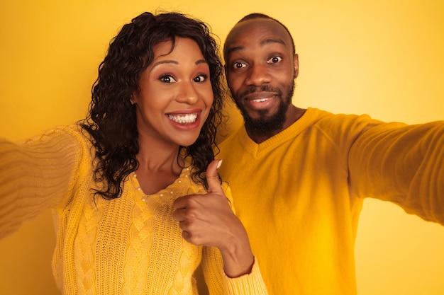 黄色の空間に明るいカジュアルな服を着た若い感情的なアフリカ系アメリカ人の男性と女性