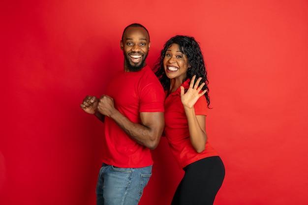 붉은 배경에 포즈를 취한 밝은 캐주얼 옷을 입은 젊은 감정적 아프리카계 미국인 남자와 여자. 아름다운 커플. 인간의 감정, 표정, 관계, 광고의 개념. 춤과 미소.