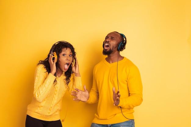 노란색 배경에 포즈 밝은 캐주얼 옷에 젊은 감정적 인 아프리카 계 미국인 남자와 여자. 아름다운 커플. 인간의 감정, 얼굴 expession, 광고의 개념. 충격적인 음악을 듣습니다.