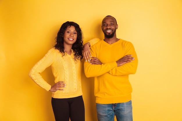 노란색 공간에 포즈 밝은 캐주얼 옷에 젊은 감정적 인 아프리카 계 미국인 남자와 여자. 아름다운 커플