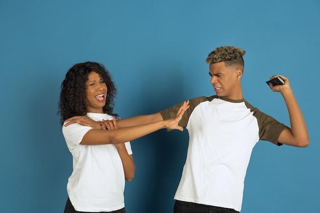 파란색 배경에 포즈 흰색 캐주얼 옷에 젊은 감정적 인 아프리카 계 미국인 남자와 여자. 아름다운 커플. 인간의 감정, 얼굴 expession, 관계, 광고의 개념. 함께 tv를 시청하세요.