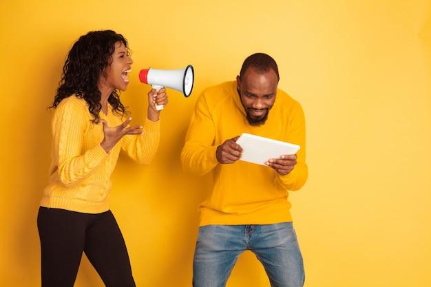 노란색 배경에 젊은 감정적 인 아프리카 계 미국인 남자와 여자