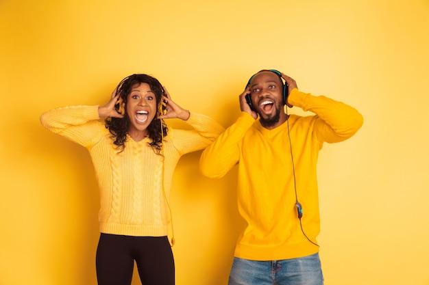 Молодой эмоциональный афро-американский мужчина и женщина на желтом фоне