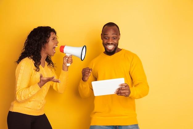 Молодой эмоциональный афро-американский мужчина и женщина на желтом