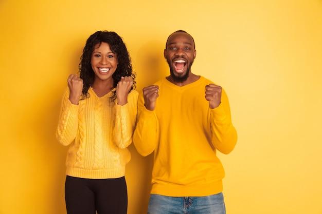 Giovane uomo afro-americano emotivo e donna in abiti casual luminosi in posa su sfondo giallo. bella coppia. concetto di emozioni umane, espansione facciale, relazioni, annuncio. buon festeggiamento.