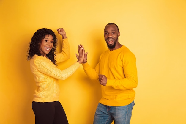Giovane uomo afro-americano emotivo e donna in abiti casual luminosi in posa su sfondo giallo. bella coppia. concetto di emozioni umane, espansione facciale, relazioni, annuncio. lavoro di squadra.