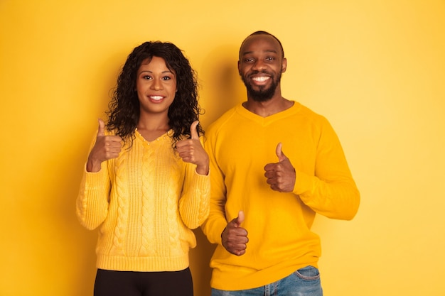 Young emotional african-american man and woman in bright casual clothes posing on yellow space. beautiful couple