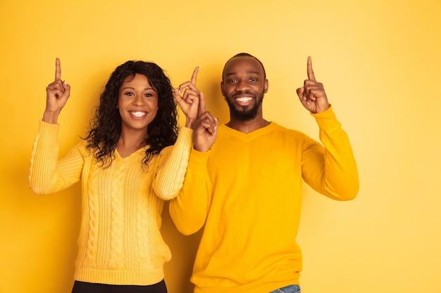 Giovane uomo afro-americano emotivo e donna in abiti casual luminosi in posa sullo spazio giallo. bella coppia