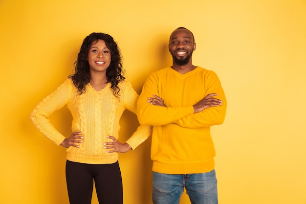 Young emotional african-american man and woman in bright casual clothes posing on yellow space
