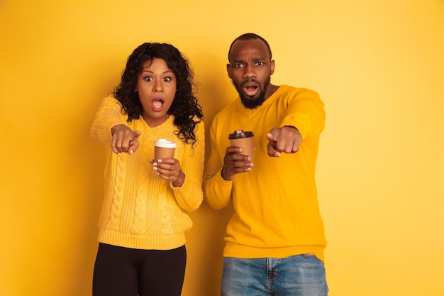 Young emotional african-american man and woman in bright casual clothes on yellow background. beautiful couple. concept of human emotions, facial expession, relations, ad. drink coffee and pointing.