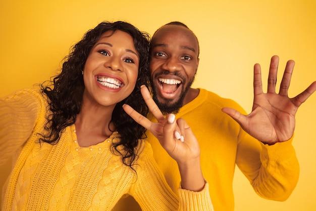 Giovane uomo afro-americano emotivo e donna in abiti casual luminosi su sfondo giallo. bella coppia. concetto di emozioni umane, espansione facciale, relazioni, annuncio. facendo selfie insieme.