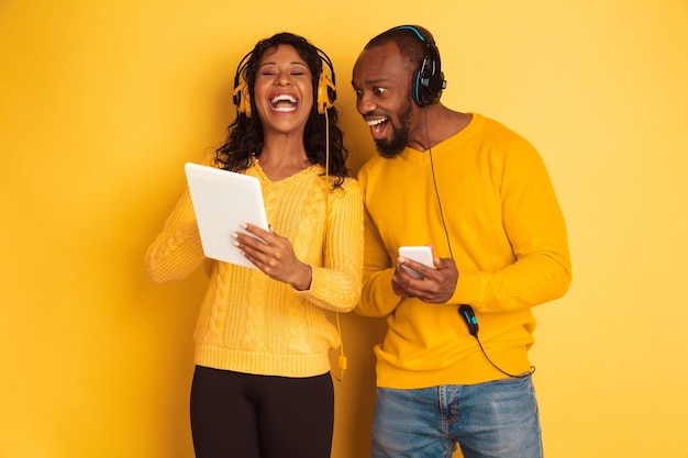Giovane uomo afro-americano emotivo e donna in abiti casual luminosi su sfondo giallo. bella coppia. concetto di emozioni umane, espansione facciale, relazioni, annuncio. utilizzando tablet e smartphone.
