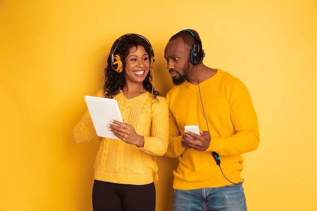 Young emotional african-american man and woman in bright casual clothes on yellow background. beautiful couple. concept of human emotions, facial expession, relations, ad. using tablet and smartphone.