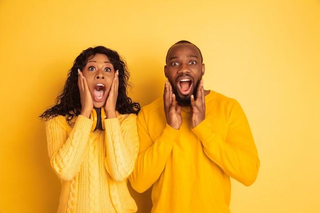Giovane uomo afro-americano emotivo e donna in abiti casual luminosi su sfondo giallo. bella coppia. concetto di emozioni umane, espansione facciale, relazioni. stupito, meravigliato, scioccato.