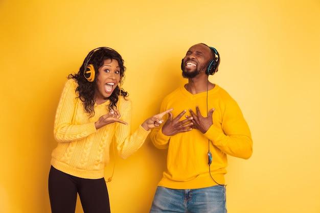 Giovane uomo afro-americano emotivo e donna in abiti casual luminosi su sfondo giallo. bella coppia. concetto di emozioni umane, espansione facciale, relazioni. sta indicando l'uomo che canta.