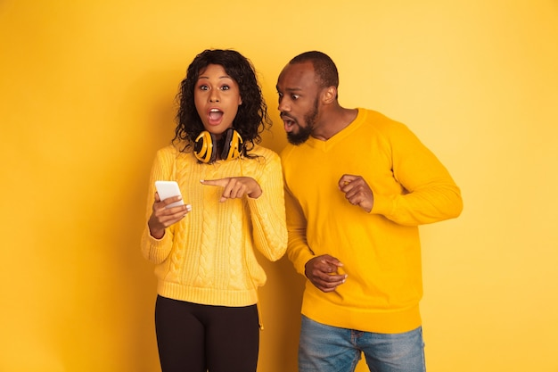 Giovane uomo afro-americano emotivo e donna in abiti casual luminosi su sfondo giallo. bella coppia. concetto di emozioni umane, espansione facciale, relazioni. puntamento scioccato sullo smartphone.