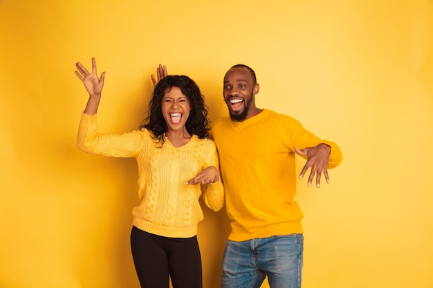 Young emotional african-american man and woman in bright casual clothes on yellow space. beautiful couple