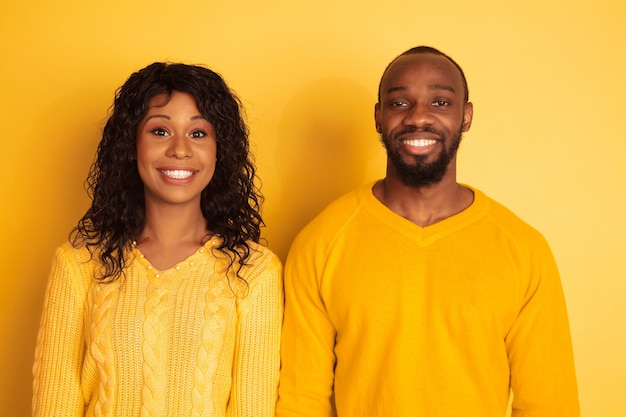 Young emotional african-american man and woman in bright casual clothes on yellow space