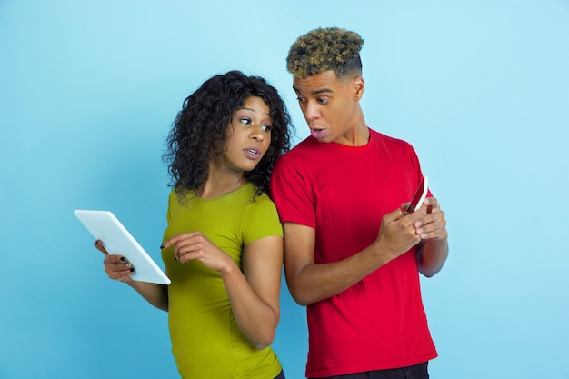 Young emotional african-american man and woman in colorful clothes using gadgets, peeping on screens on blue b