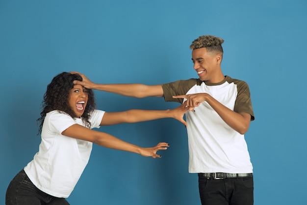 Giovane uomo afro-americano emotivo e donna in abiti casual bianchi in posa su sfondo blu. bella coppia. concetto di emozioni umane, espansione facciale, relazioni, annuncio. divertirsi, gremaces.
