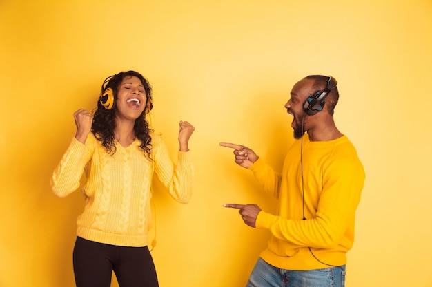 Young emotional african-american man and woman on yellow background