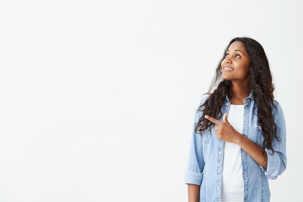 Young emotional african american woman in light-blue shirt with long black hair looking away, smiling showing teeth, pointing her finger at white wall with copy space