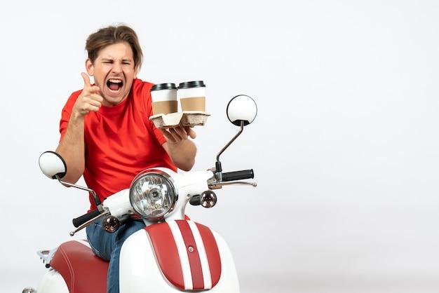 注文を保持し、黄色の壁で大丈夫ジェスチャーをしているスクーターに座っている赤い制服を着た若い感情的な野心的な宅配便の男