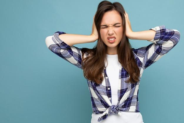 Молодая эмоциональная сердитая красивая брюнетка женщина в клетчатой рубашке изолирована на синем фоне с копией пространства и закрывает уши.