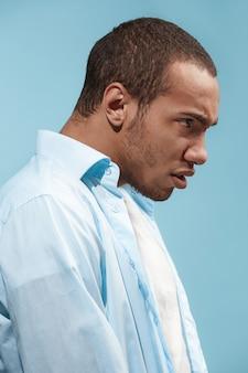 Молодой эмоциональный злой человек на синей студии