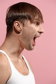 Il giovane uomo arrabbiato emotivo che grida nello spazio di studio rosa