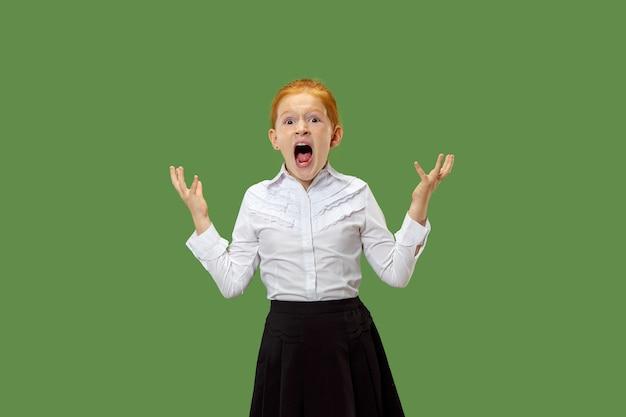 La giovane ragazza teenager arrabbiata emotiva che grida sul fondo verde dello studio