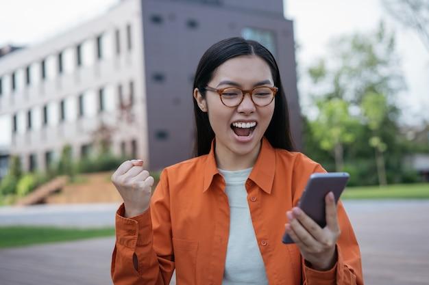 모바일 게임을 하는 행복한 여성에게 스포츠 베팅을 하기 위해 모바일 앱을 사용하는 젊은 감정적 아시아 여성