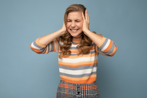 Young emotional beautiful blond curly woman with sincere emotions wearing casual striped sweater isolated on blue background with copy space and covering ears trying not to hear.
