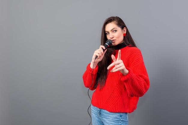 Молодая эмоциональная брюнетка с микрофоном, одетая в красный свитер, поет караоке или произносит речь, изолирована на сером