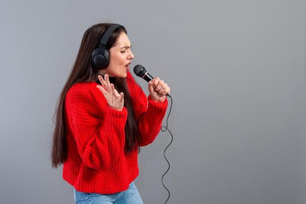 헤드폰과 빨간 스웨터를 입은 마이크가있는 젊고 감정적 인 갈색 머리는 회색에 고립 된 노래방을 노래합니다.