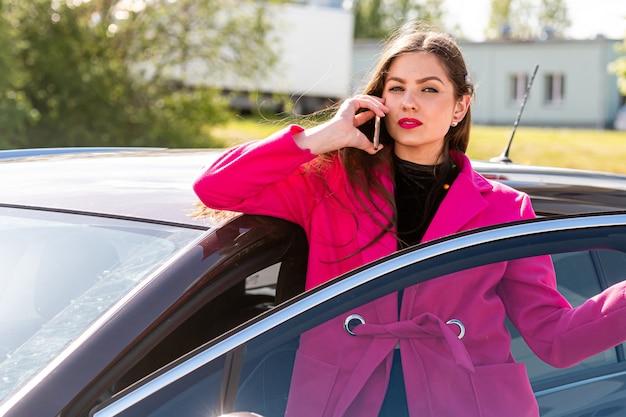 Молодая эмоциональная брюнетка выходит из машины и разговаривает по телефону