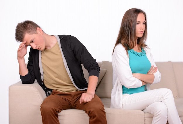 Young emotional couple sitting on sofa at home