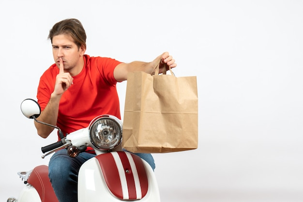 Young emotional courier guy in red uniform sitting on scooter giving paper bag making silence gesture on white wall