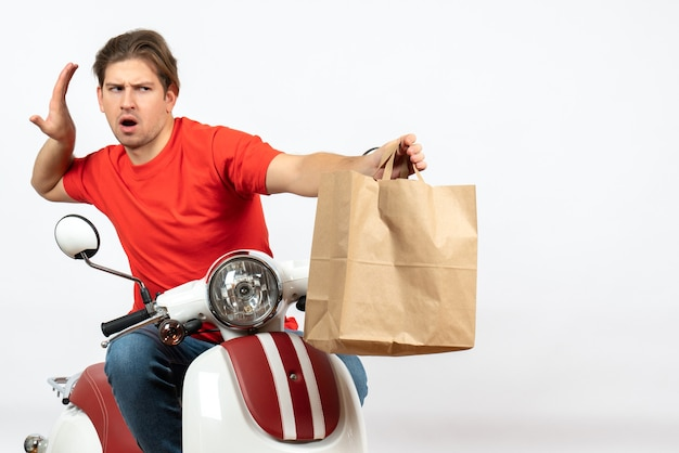 Young emotional courier guy in red uniform sitting on scooter giving paper bag on white wall