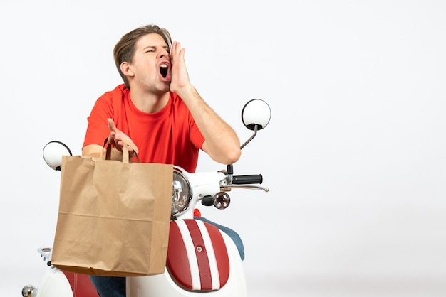 Young emotional courier guy in red uniform sitting on scooter holding paper bag calling someone on white wall